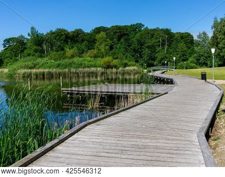 A Wooden Boardwalk Leads Along The Shores Of A Calm Blue Lake With A Small Bridge In The Background