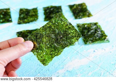 Crispy Dried Seaweed Close Up, Nori Chips Piece Of Roasted Seaweed Sheet. Healthy Food Concept.