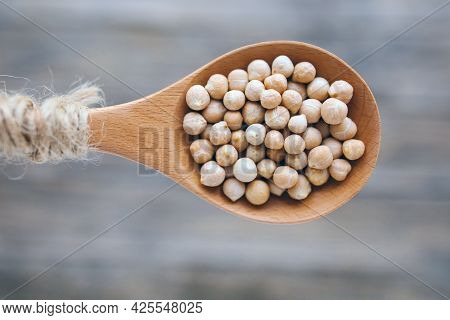 Uncooked Dried Legume Chickpeas Or Garbanzo Bean In Wooden Rustic Spoon On Blurred Background. Veget