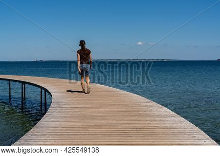 A Slim Woman Walks Along A Circular Boardwalk Leading Out And Over A Calm Blue Ocean
