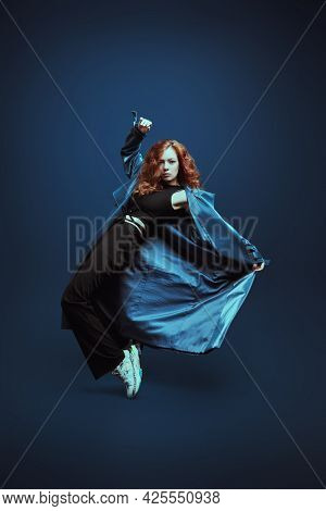 Full length portrait of a professional modern style dancer dancing at studio on a dark blue background.