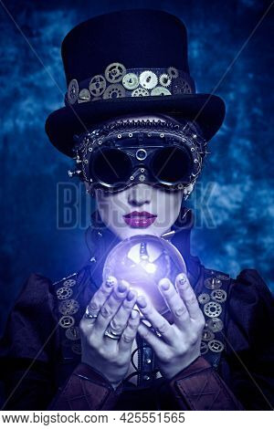 Beautiful victorian steampunk lady holds energy crystal ball on a grunge background. Fantasy world, scientific inventions.