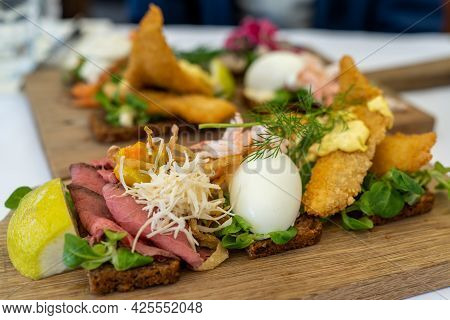 A Close Up View Of Delicious Smørebrød Sandwiches On A Wooden Platter As A Typical Scandinavian Brea