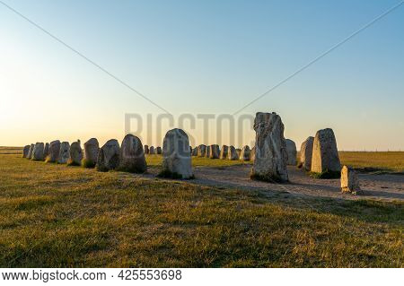 Landscape View Of The Prehistoric Ales Stenar Ship Setting On The Southern Coast Of Sweden At Sunset