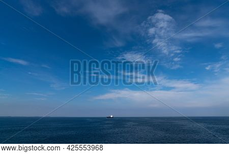 Large Freight Ship Travelling Full Steam Ahead And Approaching From Far Away On The Open Ocean