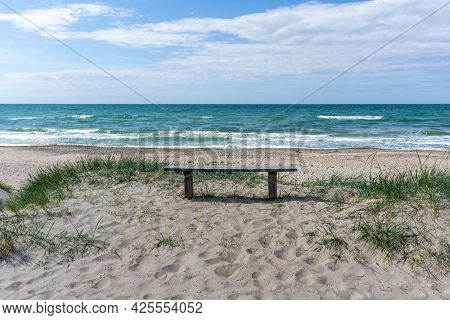 A Vertical View Of A Wooden Bench On An Idyllic Secluded Empty Beach