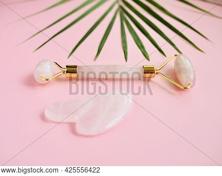 Rose Quartz Jade Face Roller. Pink Gua Sha Massage Tool On Pink Background. Facial Skin Care And Bod