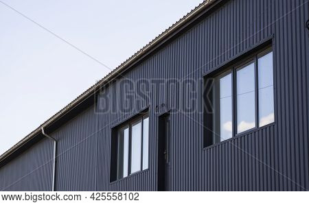 Black Corrugated Iron Sheet Used As A Facade Of A Warehouse Or Factory With A Windows. Texture Of A