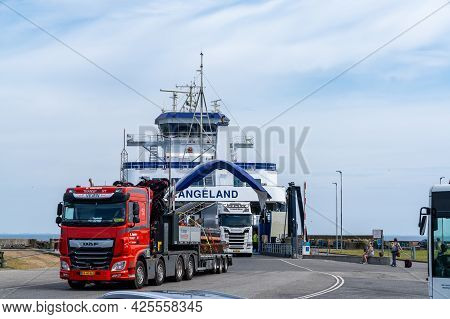 Spodsbjerg, Denmark - 10 June, 2021: The Langeland Ferry Unloading Large Trucks And Lorries At The S