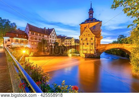 Bamberg, Franconia. Obere Brucke And Regnitz River Dusk Illuminated, Old Town. Bavaria, Germany City
