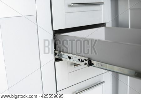 Stainless Telescopic Bayonet Drawer Slide Guides, Installed On A Kitchen Cabinet From Gray Chipboard