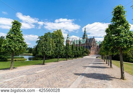 Hillerod, Denmark - 16 June, 2021: Long Tree-lined Alley Leading To The Frederiksborg Castle In Hill