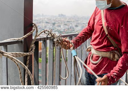 Construction Workers Holding Steel Hooks Connecting With Rope For Self Absorber Safety Device Equipm