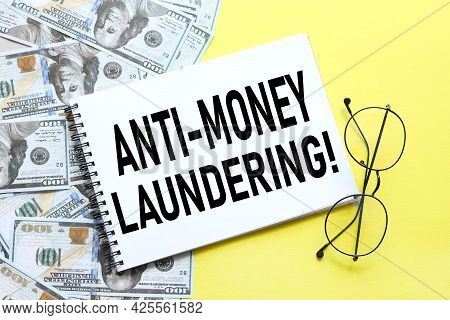 Anti-money Laundering Aml. Background With Money, Dollar Bills And Yellow Background. Text On Notepa