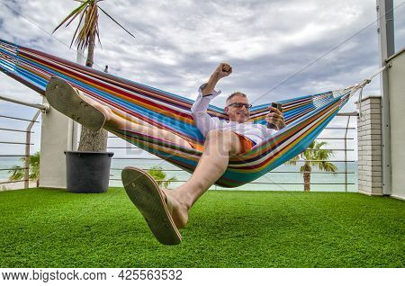 Telecommuter Receiving Good News By The Smartphone While Lying In A Hammock In A Balcony By The Sea