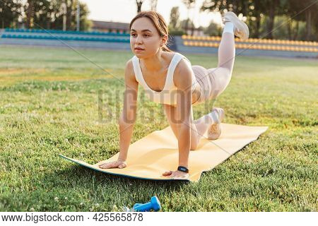 Fitness Girl Doing Leg Workout On Yoga Mat At Outdoor Stadium, Fit Woman Wearing White Top And Beige