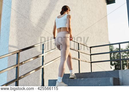 Back View Of Slim Female With Good Shape Wearing Stylish Sporty Clothing, Beige Leggings And Top, Go