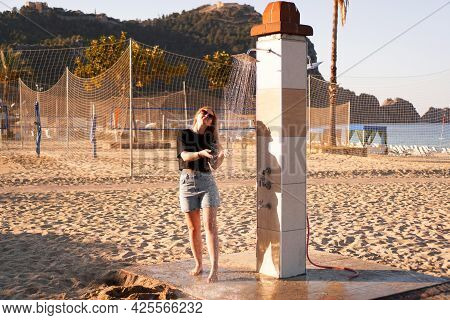 A Girl In Shorts And A Black T-shirt On The Beach Near The Shower. Shower On The Beach. Nearby There