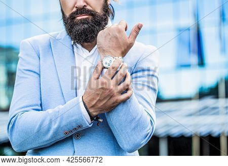 Watch In A Man. Businessman Points To His Watch On The Background Of The Town. Man Holds His Watch.
