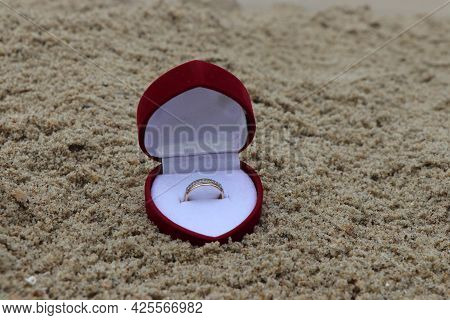 A Ring In A Box On A Sandy Beach. A Romantic Way To Propose. An Engagement Ring. Engagement Ring