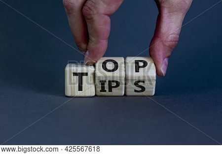 Top Tips Symbol. Businessman Turns Wooden Cubes With Words 'top Tips'. Beautiful Grey Background. To