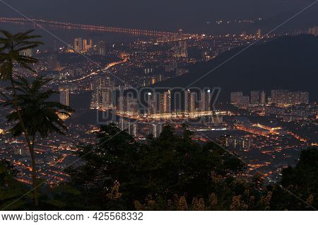 The Silhouette Of Palm Trees With A Night View Of The City Of Air Itam On The Island Of Penang Malay