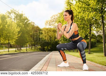 Beautiful Woman Doing Fitness Exercise In Morning Outdoors