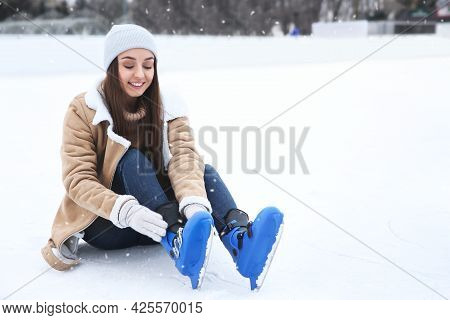 Happy Woman Wearing Figure Skates While Sitting On Ice Rink Outdoors. Space For Text