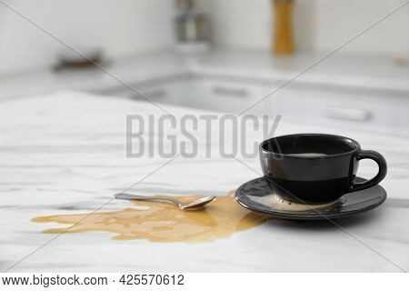 Cup And Spilled Coffee On White Marble Table In Kitchen, Space For Text