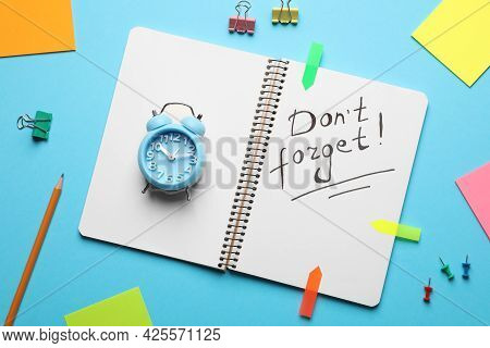 Alarm Clock, Stationery And Notebook With Phrase Don't Forget On Light Blue Background, Flat Lay. Re