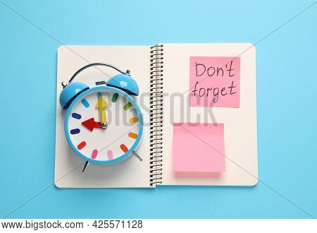 Alarm Clock, Notebook And Reminder Note With Phrase Don't Forget On Light Blue Background, Top View