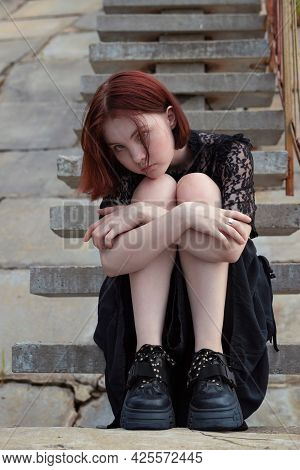 A Young Girl With Red Hair, In A Black Lace Dress, With A Piercing In Her Nose, Sits On A Concrete G