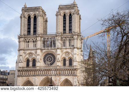 Famous Facade Of Notre-dame De Paris With Tower Crane On Background