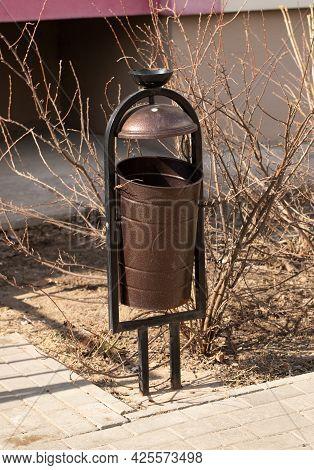 Metallic Brown Wastebasket In Sunny City Outdoors In Spring.