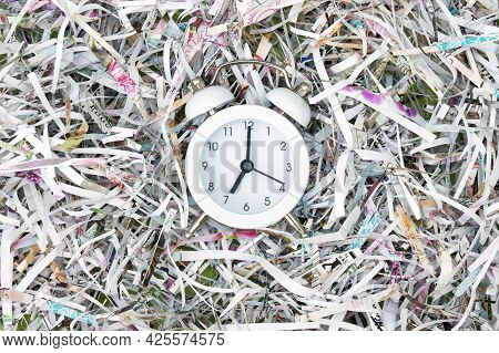 Vintage White Alarm Clock On A Background Of Shredded Paper. Selective Focus Of The Image.