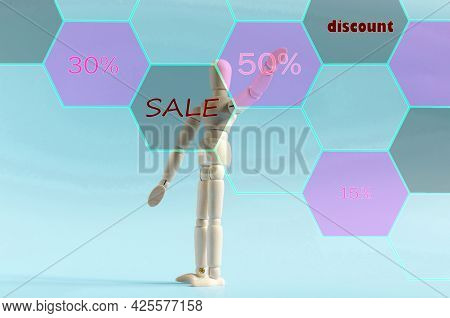 The Figure Of A Wooden Man Pointing With His Hand At An Interactive Button With The Inscription