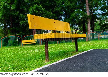 A Yellow Plastic Bench Stands In The Park Next To A Black Rubber Coating. Against The Backdrop Of Gr