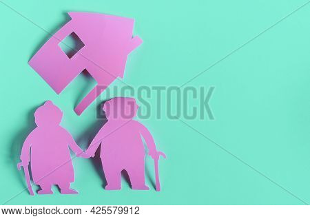Bright Red Figures Of Two Elderly People And A House On A Colored Background. The Concept Of Family