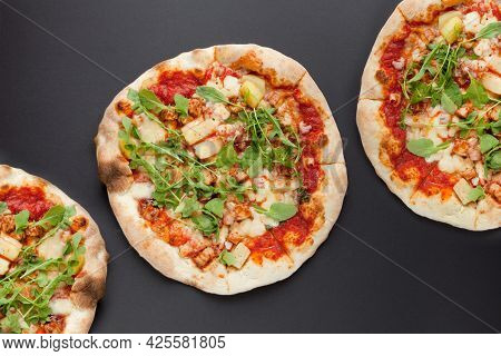 Three Pizzas With Smoked Ham And Rucola On Black Background. Tasty Thin Italian Pizza With Meat On D
