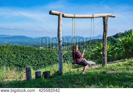 Asian Fat Guy Sitting On Wooden Swing With Beautiful Landscape View On Phu Lamduan At Loei Thailand.