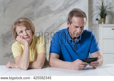Elderly Couple, Senior Woman Wife Looking Unhappy Bored While Her Retired Man Husband Ignoring Her,