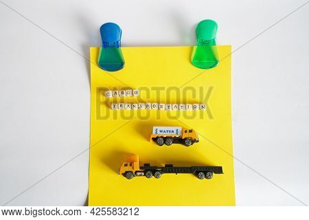 An Advertisement For Trucking Services Hangs On Magnetic Clips On A White Bulletin Board. Toy Trucks