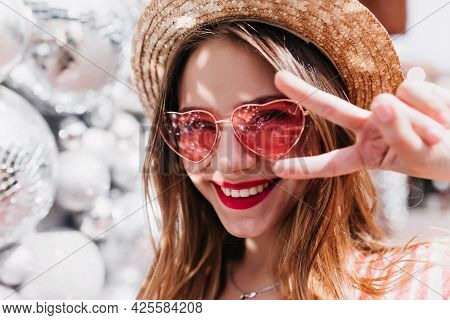 Close-up Portrait Of Good-humoured White Woman Posing With Peace Sign On Blur Background. Photo Of R