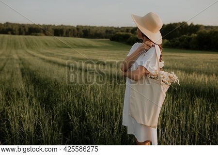 A Girl In A White Dress Stands In A Green Field Looking Into The Distance. A Young Woman Stands In A