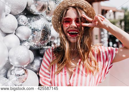 Ecstatic European Girl Laughing While Posing Beside Sparkle Balls. Outdoor Portrait Of Beautiful Goo