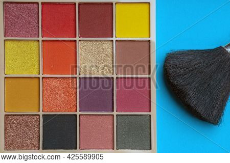 Eyeshadow And Eyes In Square Shape. There's A Brush Next To It. On A Blue Background.