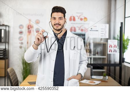 Confident Indian Medical Worker In White Lab Coat Holding Stethoscope And Smiling On Camera. Portrai