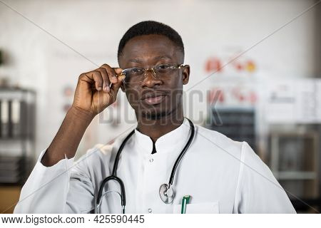 Black Health Care Worker Adjusting His Eyglasses While Posing At Bright Hospital Room. Qulified Doct