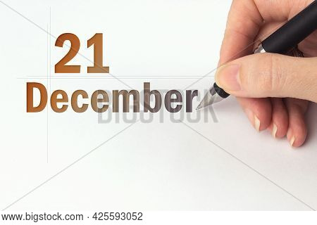 December 21st . Day 21 Of Month, Calendar Date. The Hand Holds A Black Pen And Writes The Calendar D