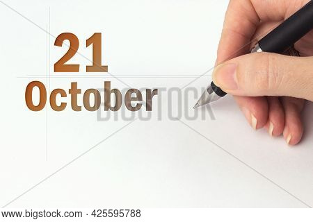 October 21st . Day 21 Of Month, Calendar Date. The Hand Holds A Black Pen And Writes The Calendar Da